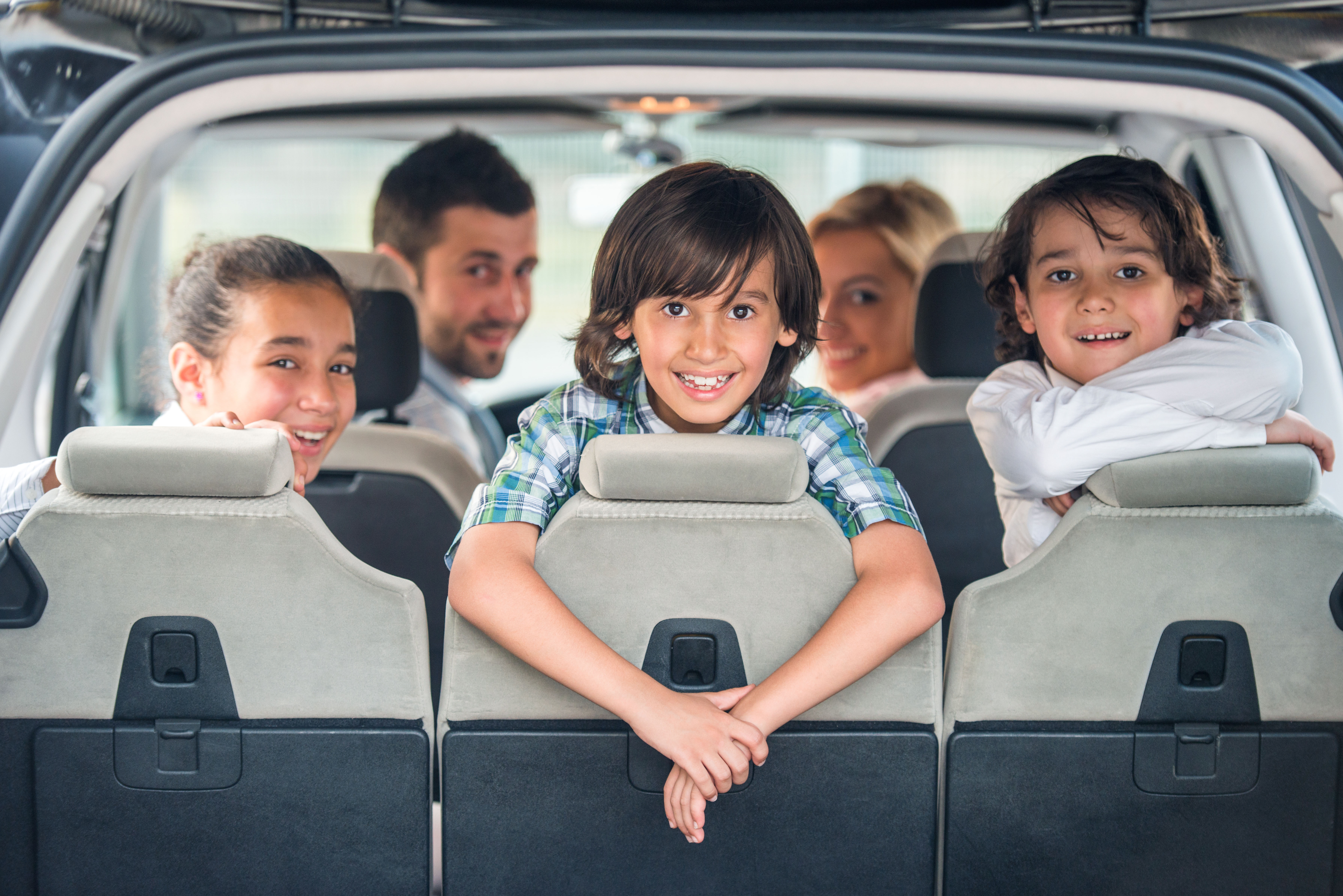 Playful kids posing in the back of a car